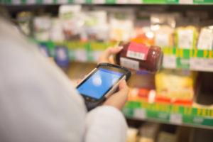 Supermarket Clerk Uses Handheld Inventory Scanner