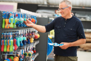 Man looks at Shelf Labels in a Pet Store
